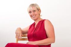 Bella metà di donna invecchiata europea in vestito rosso che si siede o rilassata Immagini Stock Libere da Diritti