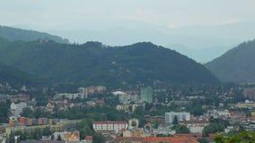 Bella montagna coperta dalla foresta densa vicino ad area della città nel giorno di primavera, paesaggio urbano calmo stock footage