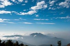 Bella natura, cielo blu, montagne nebbiose e nuvole Fotografia Stock