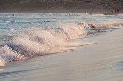 Bella onda del mare sulla spiaggia sabbiosa al tramonto di estate fotografia stock