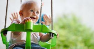 Bella oscillazione del bambino all'aperto con preoccuparsi faimly immagine stock libera da diritti