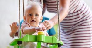 Bella oscillazione del bambino all'aperto con preoccuparsi faimly fotografie stock libere da diritti