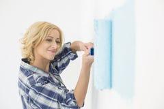 Bella parete della pittura della donna con il rullo di pittura immagini stock