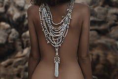 Bella parte posteriore della giovane donna con la fine etnica della collana su Fotografia Stock