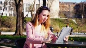 Bella persona femminile che chiacchiera con gli amici dalla compressa in parco Fotografia Stock Libera da Diritti