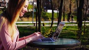 Bella persona femminile che chiacchiera con gli amici dalla compressa in parco Fotografie Stock Libere da Diritti