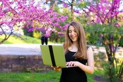 Bella persona femminile che utilizza computer portatile nel fondo di fioritura Immagini Stock