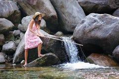 Bella pesca della giovane donna in un fiume Fotografia Stock Libera da Diritti