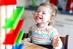 Bella piccola neonata sveglia adorabile che gioca con i giocattoli educativi a casa o la scuola materna Immagini Stock Libere da Diritti