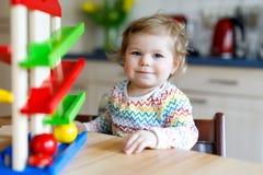 Bella piccola neonata sveglia adorabile che gioca con i giocattoli educativi a casa o la scuola materna Immagine Stock