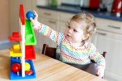 Bella piccola neonata sveglia adorabile che gioca con i giocattoli educativi a casa o la scuola materna Immagine Stock Libera da Diritti