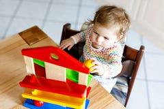 Bella piccola neonata sveglia adorabile che gioca con i giocattoli educativi a casa o la scuola materna Fotografia Stock