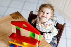 Bella piccola neonata sveglia adorabile che gioca con i giocattoli educativi a casa o la scuola materna Fotografie Stock
