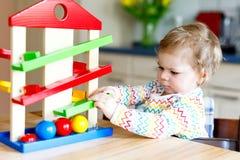 Bella piccola neonata sveglia adorabile che gioca con i giocattoli educativi a casa o la scuola materna Fotografia Stock Libera da Diritti