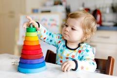 Bella piccola neonata sveglia adorabile che gioca con la piramide di legno educativa del giocattolo dell'arcobaleno fotografia stock libera da diritti