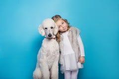 Bella piccola principessa con il cane Amicizia pets Ritratto dello studio sopra fondo blu fotografie stock libere da diritti