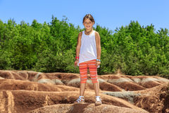 Bella piccola ragazza sorridente allegra che sta contro il fondo dei calanchi di Cheltenham il giorno caldo soleggiato Fotografie Stock Libere da Diritti