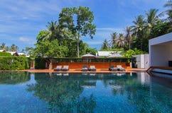 Bella piscina nella località di soggiorno con le sedie di spiaggia vicino al mare immagine stock