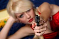 Bella pistola della holding della giovane donna, fuoco sulla pistola Immagini Stock Libere da Diritti