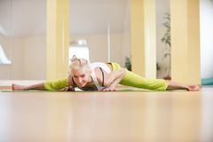 Bella posa sportiva di angolo diritto di Samakonasana di asana di yoga di pratiche della donna degli Yogi di misura nella stanza  Fotografie Stock