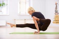 Bella posa sportiva di Eka Hasta Bhujasana di asana di yoga di pratiche della donna degli Yogi di misura nella stanza di forma fi Immagine Stock Libera da Diritti