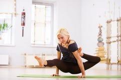 Bella posa sportiva di Eka Hasta Bhujasana di asana di yoga di pratiche della donna degli Yogi di misura nella stanza di forma fi Immagini Stock Libere da Diritti