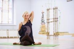 Bella posa sportiva di Garudasana Eagle di asana di yoga di pratiche della donna degli Yogi di misura nella stanza di forma fisic Fotografia Stock