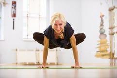 Bella posa sportiva di Padma Bakasana Lotus Crane di asana di yoga di pratiche della donna degli Yogi di misura nella stanza di f Fotografia Stock