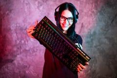 Bella pro ragazza amichevole che posa con una tastiera in sue mani, vetri d'uso della fiamma del Gamer Ragazza attraente del geek immagine stock