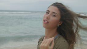 Bella ragazza abbronzata con capelli lunghi che stanno sulla spiaggia sabbiosa archivi video