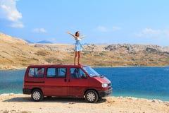 Bella ragazza abbronzata in un vestito blu che sta su un tetto del furgone rosso Fotografie Stock Libere da Diritti