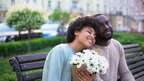Bella ragazza africana che ritiene soddisfatta dei fiori alla data, abbracciare dolce delle coppie archivi video