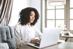 Bella ragazza afroamericana che si siede nel ristorante con il computer portatile Ragazza graziosa che lavora al suo computer in  Immagine Stock Libera da Diritti