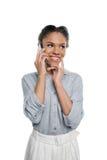 Bella ragazza afroamericana sorridente che parla sullo smartphone e sul distogliere lo sguardo Fotografia Stock
