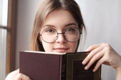 Bella ragazza alla finestra che legge un libro Fotografia Stock