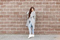 Bella ragazza alla moda in cappotto grigio e jeans vicino ad un mattone immagini stock