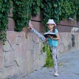 Bella ragazza alla moda che sta nelle spaccature e nella lettura Fotografia Stock