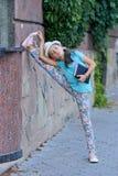 Bella ragazza alla moda che sta nelle spaccature e nella lettura Fotografie Stock