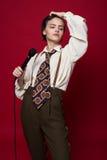 Bella ragazza alla moda del cantante in retro cappotto, legame e pantaloni con il microfono in mani che posano sul fondo rosso fotografia stock