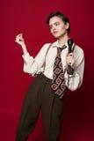 Bella ragazza alla moda del cantante in retro cappotto, legame e pantaloni con il microfono in mani che posano sul fondo rosso immagini stock