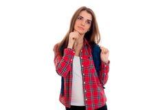 Bella ragazza alla moda dello studente con lo zaino sulla sua posa delle spalle isolato su fondo bianco Fotografie Stock