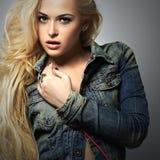 Bella ragazza alla moda in jeans Ragazza di bellezza con capelli ricci usura del denim immagini stock
