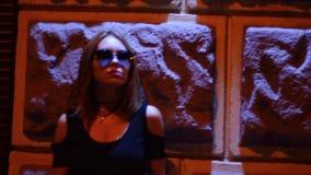 Bella ragazza alla moda nel valore di vetro alla notte sulla via vicino ad una parete video d archivio