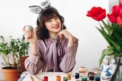 Bella ragazza alla moda in orecchie del coniglietto che sorride e che dipinge pasqua fotografia stock libera da diritti