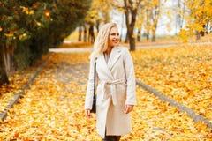 Bella ragazza alla moda in un cappotto classico d'avanguardia con una borsa fotografie stock libere da diritti