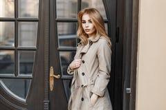 Bella ragazza alla moda in un cappotto d'avanguardia vicino all'hotel fotografie stock