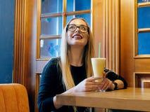 Bella ragazza alla tavola in un caffè che aspetta per incontrarsi fotografia stock