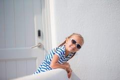 Bella ragazza alla via del villaggio tradizionale greco tipico con le pareti bianche e le porte variopinte sull'isola greca Immagini Stock Libere da Diritti