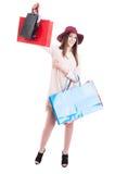 Bella ragazza allegra in attrezzatura d'avanguardia che aumenta sui sacchetti della spesa Fotografia Stock