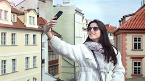 Bella ragazza allegra che sorride prendendo selfie facendo uso dello smartphone circondato da paesaggio urbano europeo archivi video